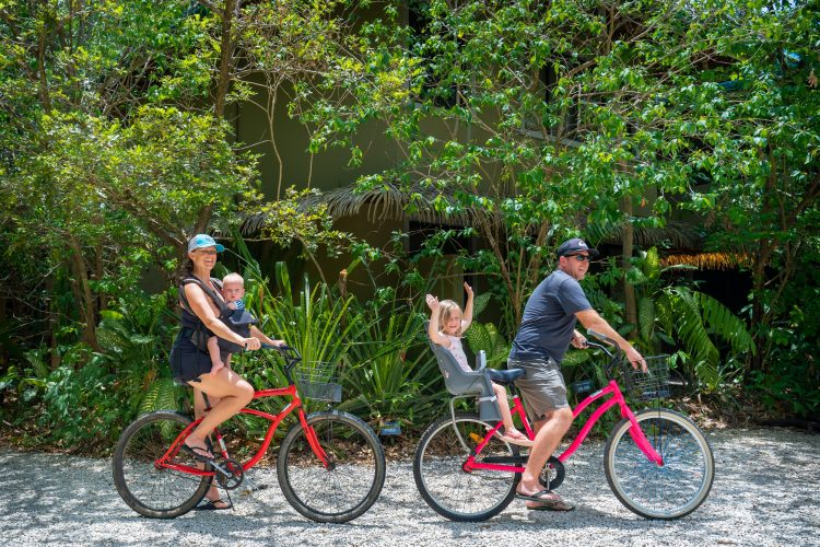 Ben, Kelly and the kids riding red bicycles in an unpaved Nosara Costa Rica